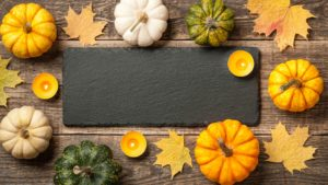 Thanksgiving background with pumpkins, autumn leaves and candles